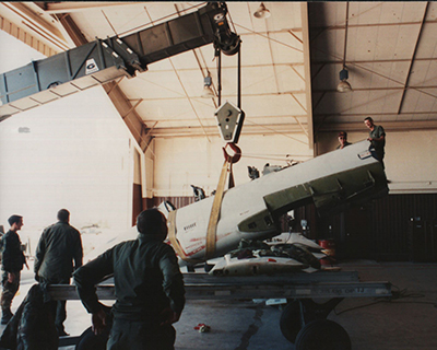 SDANG airmen lifts part of the aircraft using a crane to perform maintenance.